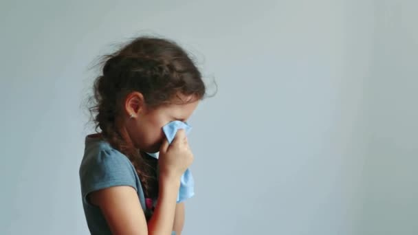 girl child sneezes into handkerchief on a gray background. little girl get cold and blow her nose. teen girl cold flu concept lifestyle