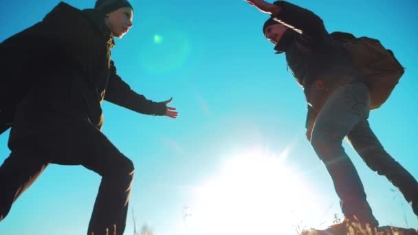 teamwork tourists business travel trip lends a helping hand. two men with backpacks hiking help each lifestyle other silhouette in mountains with sunlight. slow motion video. teamwork friendship