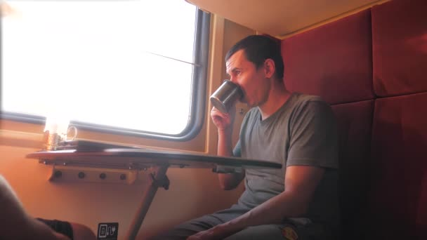 man is sitting on the train carriage holding a Railway and drinking coffee and tea. slow motion video. two men drinking tea on lifestyle the train talking the train social media . man with smartphones