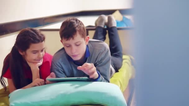 little boy and girl are playing and dog on the tablet lying on the bed. boy and girl teens social media lifestyle internet on a tablet indoors. children and tablet concept
