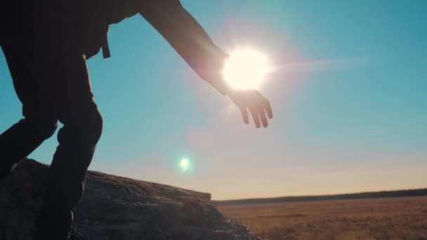 teamwork business travel trip. two men with backpacks hiking help each other silhouette in mountains with sunlight. slow motion video. teamwork friendship hiking help each other trust assistance