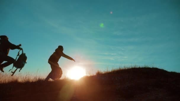 teamwork run jump throw backpacks happiness joy victory success. Two hikers enjoying sunrise walking from top of a mountain and dog. Two hikers with backpacks climbing a peak on cloud sky background