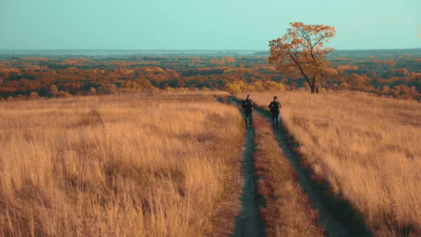 people tourists travel in nature the autumn go on the road path adventure. slow motion lifestyle video. two hiker with outdoor backpacks hiking. tourist concept the travel man tourism