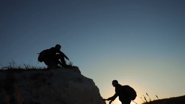 silhouette two men teamwork tourists climber climbs a mountain. walking tourist hiking adventure climbers sunset climb the mountain . slow motion video. hiker sunlight on top win victory the hill