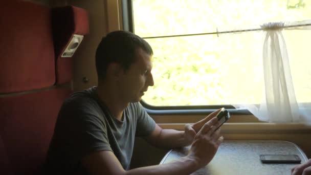 muž cestovatel relaxaci na vlak do přátel a usmívá se prostřednictvím obrázků přes sociální média. zpomalené video. ukládání fotografií pomocí mobilního telefonu při jízdě domů v kupé vagónu vlaku