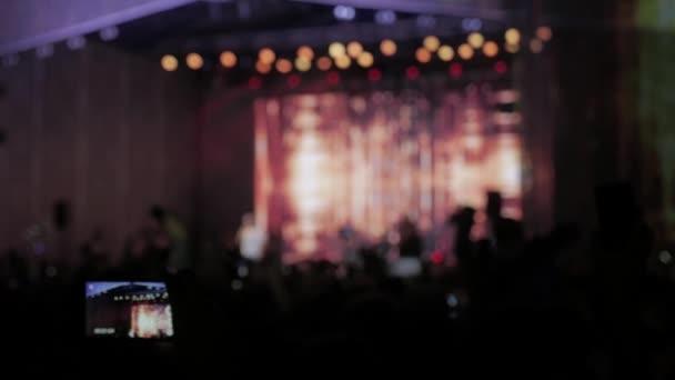 Publikum beim Konzert - Sommermusikfestival. Konzertbesucher, die ein Konzert besuchen, sehen Silhouetten von Menschen, die von Bühnenlichtern beleuchtet werden. Das Publikum verfolgt das Konzert live auf der Bühne