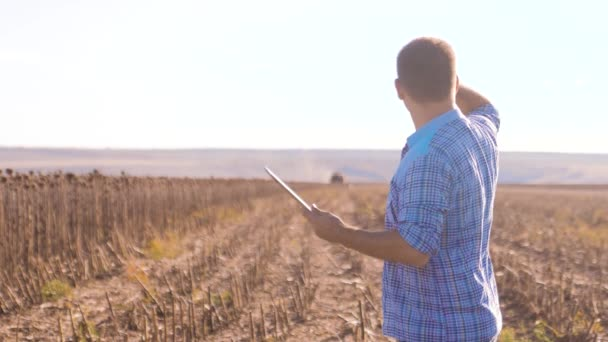 Farmer Smart farming works man read or analysis harvest sunflower a report in tablet computer on a agriculture field with vintage tone on a sunlight. lifestyle the combine harvester plows a field