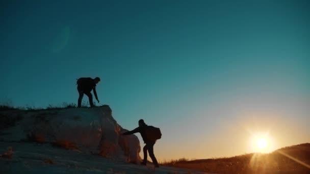 Týmová práce turistů. přátelství turistické pomoci každé jiné důvěry pomoci silueta v horách. Backpacker pomáhá svému příteli k lezení na skále. dva cestující pomoci, natahuje ruku. turistické vítězství