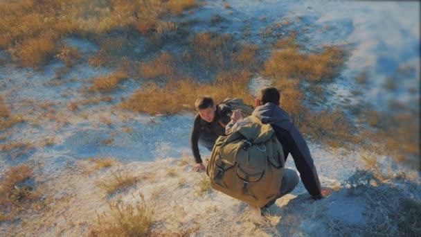 Týmová práce turistů. zpomalené video. přátelství turistické pomoci každé jiné důvěry pomoci silueta v horách. Backpacker pomáhá svému příteli stoupat životní styl rock. dva cestující Nápověda