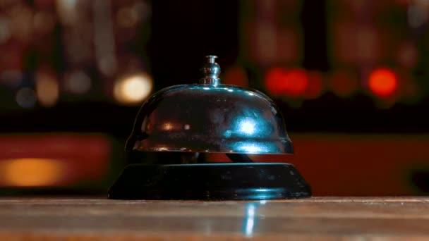 Hotel ring na dřevěný stůl pozadí. Bell vintage služba volání s rukou. Restaurace zvon vinobraní na bokeh. Vintage hotel recepce service desk bell lifestyle