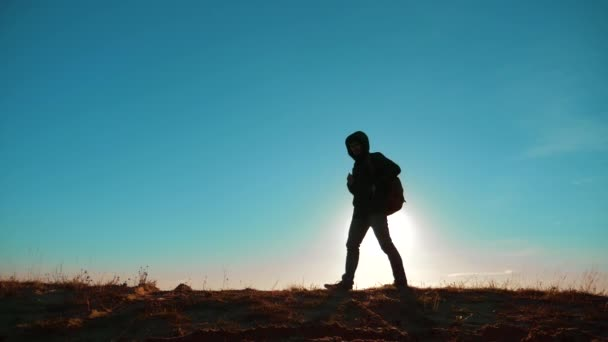 Male man worth it tourist with backpack smartphone navigation sunlight stands on top of a mountain lifestyle . slow motion video. man silhouette at sunset . hikers adventure and the go walking. travel