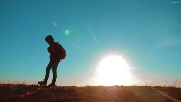 Male man walking worth lifestyle it tourist with backpack sunlight adventure stands on top of a mountain . slow motion video. man silhouette at sunset . hikers adventure and the go . travel silhouette