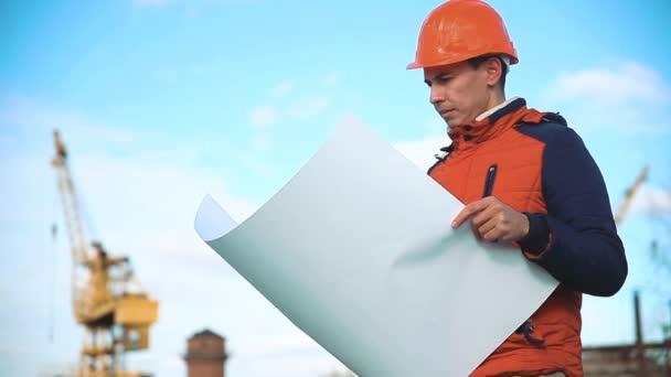 Technické tvůrce muž poradenství lidem na stavební lokality hospodářství plán v ruce. Stavební inspektor životního stylu. Senior inženýr zimní bunda muž v obleku a helmu venkovní. stavebnictví