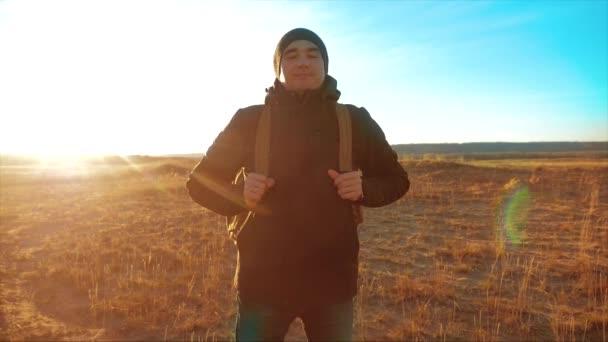Silueta tramp muž s batohem. Steadicam motion video slunečního záření slunce osoba boční pohled k úspěšné životní styl. osamělý muž s slunce pozadím. Cestování a úspěch konceptu