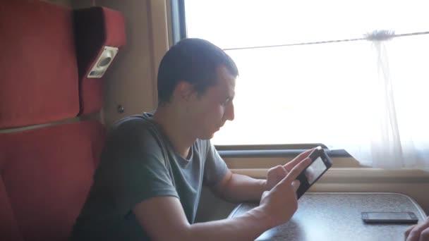 muž cestovatel relaxaci na vlak do přátel a usmívá se prostřednictvím obrázků životního stylu prostřednictvím sociálních médií. zpomalené video. ukládání fotografií pomocí mobilního telefonu při jízdě domů vlakem vozu