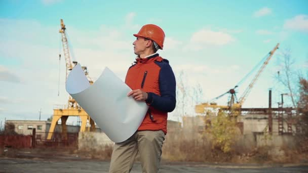 Engineering builder man Consulting People on construction site holding blueprint in his hand. Building inspector lifestyle . Senior engineer Winter Jacket man in suit and helmet outdoor . construction