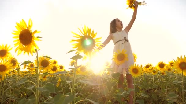 Cute child girl in yellow garden of sunflowers sunlight in lifestyle summer. beautiful sunset little girl in sunflowers. slow motion video. girl teenager and sunflowers field concept agriculture
