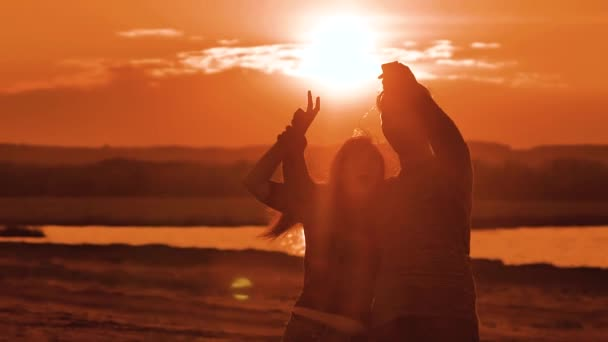 Couple silhouette doing selfie outdoors. Man and girl of best friends taking selfie during sunset. Modern concept of friendship with new trends and technology. Romantic silhouette couple doing selfie