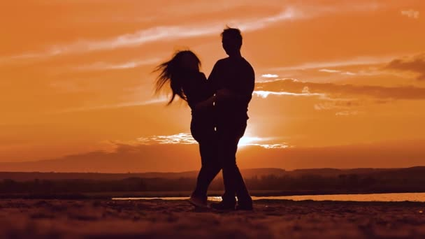 silhouette man and girl of a happy young married couple slow dancing outside at sunset. Couple enjoying on nature the beach in sunset sunrise time. concept romance lifestyle love friendship