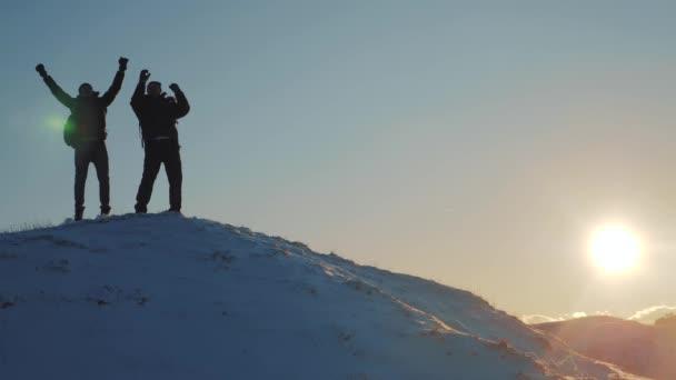 koncepce týmové práce obchodní cesty. Dva turisté dvou horolezců na vrchol hory zvedli ruce nahoru zimní hory sněhu. Siluety tým na vrchol hory. Sport a aktivní život