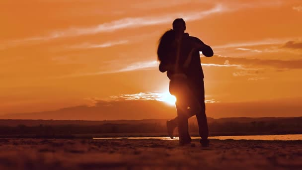 silhouette man and girl of a happy young married couple slow dancing outside at sunset. Couple enjoying on nature the beach in sunset sunrise time. concept lifestyle romance love friendship