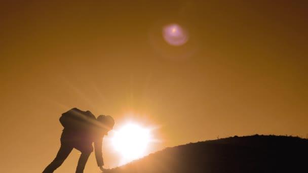 Týmová práce lidí turisté obchodní cesty cesty podává pomocnou ruku. dva muži s batohy turistické pomoci každý silueta v horách s slunečního světla. pomalé videa pohybu životní styl. Týmová práce