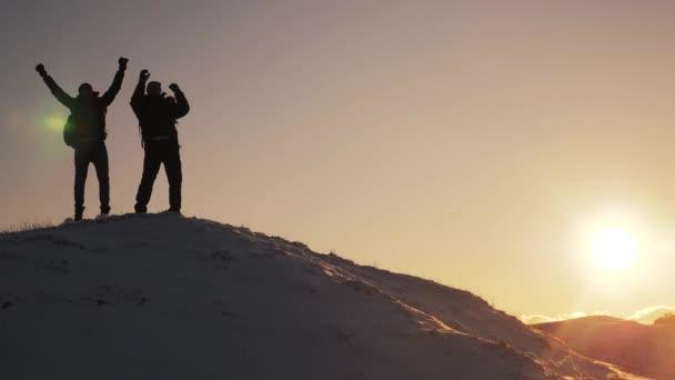 koncepce týmové práce obchodní cesty. Dva turisté dvou horolezců na vrchol hory zvedli ruce nahoru zimní hory sněhu. Siluety tým na vrchol hory. Sport a aktivní život koncepce