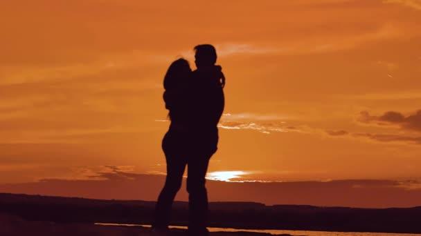 átölelve a naplemente napfény silhouette szerelmes pár. családi szeretet szerelem fogalmát. Pár férfi és a lány sziluettek a szerelem romantikus párok szerető pár átölelve csók. életmód-férfi és nő