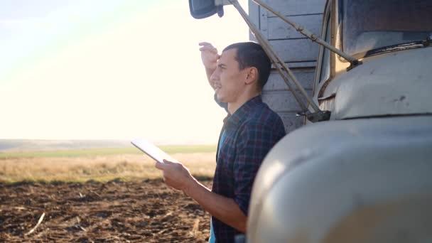 Smart Farming. Der Fahrer steht mit einem digitalen Tablet in der Nähe des Lastwagens. Zeitlupenvideo. Porträt Geschäftsmann Bauer Lebensstil steht auf dem Feld Erntezeit Auto. Fahrer Landwirt nutzt eine