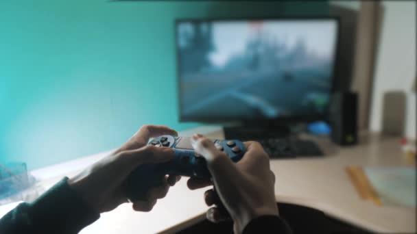 fiú játszik a vezérlő botkormány gamepad a konzol számítógép. Lejátszás videojáték-konzol a TV-ben. Kézzel tart új joystick online játékkonzol tv. életmód Gamer játék gamepad