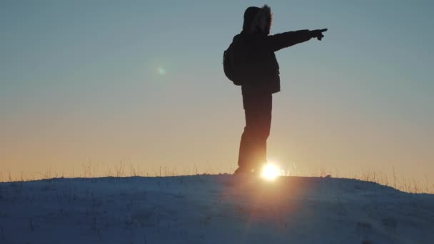 victory business travel concept. man traveler hiking in winter mountains. trekking in wintertime cold snowy weather. rock man climber silhouette over natural colorful sky with lifestyle bright sunset