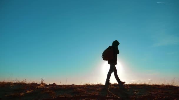 Muž muž stojí za to turistické lifestyle batoh sluneční světlo dobrodružství stojí na vrcholu hory. zpomalené video. muž silueta při západu slunce. Pěší turisté dobrodružství a cestách. cestovní silueta