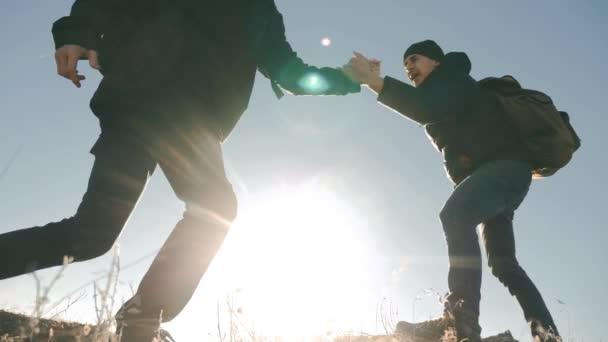 Týmová práce turistů životní styl obchodní cesty cesty podává pomocnou ruku. dva muži s batohy turistické pomoci každý silueta v horách s slunečního světla. zpomalené video. Týmová práce přátelství