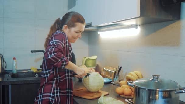 Frau in der Küche bei der Vorbereitung eines Essenskonzepts. Mädchen in der Küche schneidet Kohl mit einem Messer. Vegetarisch kochen und gesund ernähren. Mädchen zu Hause in der Küche Lifestyle Zeitlupe Video