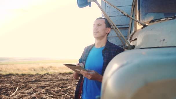 Smart Farming. Der Fahrer steht mit einem digitalen Tablet in der Nähe des Lastwagens. Zeitlupenvideo. Porträt Geschäftsmann Bauer steht auf dem Feld Erntewagen. Landwirt fährt einen Lebensstil