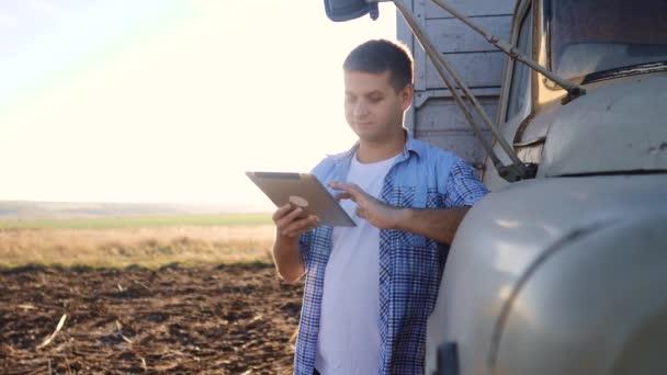 Smart-Farming-Fahrer. Der Fahrer steht mit einem digitalen Tablet in der Nähe des Lastwagens. Lifestyle-Video in Zeitlupe. Porträt Geschäftsmann Bauer steht auf dem Feld Erntewagen. Fahrer