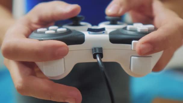 férfi játszik gamepad kezét a tv játékkonzol. Kézzel tart játszik játékkonzol tv új joystick. Gamer játék a játékvezérlő-vezérlővel. A játék gazdaság szimulátor böngészhetsz az ember. Az a személy, billentyűzet