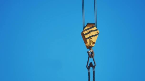 gelbe Hubkran Haken blauer Himmel Hintergrund. Kranhaken Konstruktion Konzept Lifestyle
