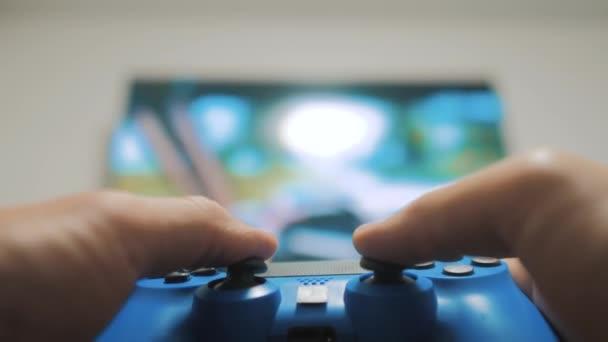 Playing videó konzol a TV-ben. Kézzel tart játszik játékkonzol tv új joystick. életmód Gamer játék gamepad-vezérlővel. A játék gazdaság szimulátor böngészhetsz az ember. Billentyűzet, joystick személy