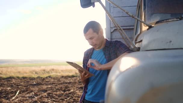 Smart Farming. Der Fahrer steht mit einem digitalen Tablet in der Nähe des Lastwagens. Porträt Geschäftsmann Bauer steht auf dem Feld Erntewagen. Landwirt fährt mit Tablet-Computer auf