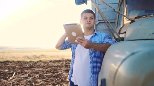 Smart Farming. Der Fahrer steht mit einem digitalen Tablet in der Nähe des Lastwagens. Zeitlupenvideo. Porträt Geschäftsmann Bauer steht auf dem Feld Erntewagen. Fahrer Landwirt nutzt eine