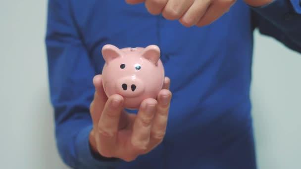 üzletember teszi megtakarítások érmék helyezi a malacka bank. Piggy bank üzleti koncepció életmód. Slow motion videót. pénzt takaríthatunk meg a befektetést a jövőben. Banki, befektetési és finanszírozási. kéz