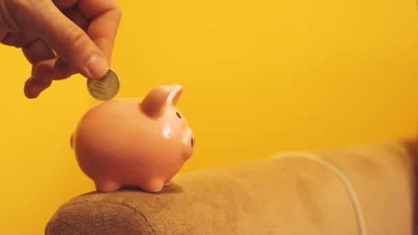 Piggy bank üzleti koncepció. A kezét a napokban egy érmét egy életmód malacka bank sárga háttéren. pénzt takaríthatunk meg a befektetést a jövőben. Banki, befektetési és finanszírozási koncepciót a