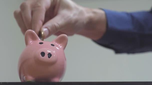 podnikatel dělá úspory klade mince prasátko. obchodní koncept prasátko. zpomalené video. Úspora peněz je investice do budoucna. životní styl bankovní investice a finance. ruka je