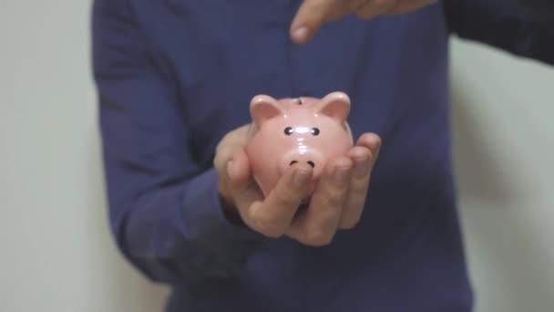 üzletember teszi megtakarítások érmék helyezi a malacka bank. Piggy bank üzleti koncepció. Slow motion videót. életmód, pénzt takaríthatunk meg a befektetést a jövőben. Banki, befektetési és finanszírozási. kéz