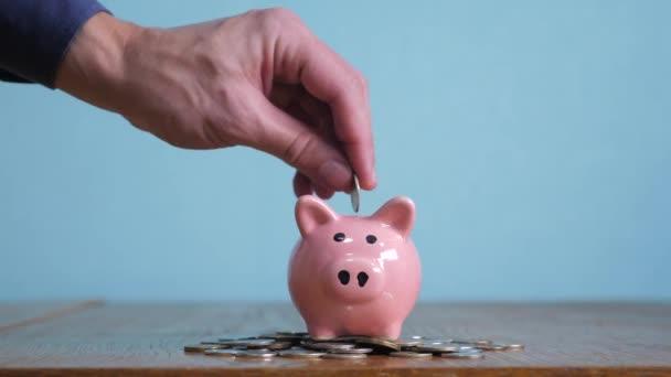 Piggy bank üzleti állva egy halom érmék koncepció. A kezét a napokban egy érmét a piggy bank sárga háttéren. pénzt takaríthatunk meg a befektetést a jövőben életmód. Banki befektetési és