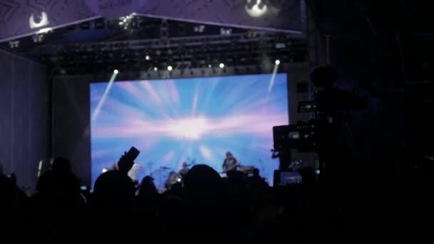 Dav lidí na koncert hudby. Jásající dav se fotí smartphone před světlé barevné MXC. siluety koncert dav před světlé fázi světla. životní styl dav