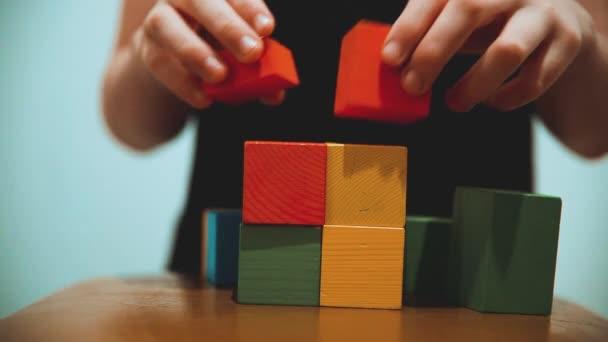 malý chlapec sbírá kostky. malý chlapec hraje s hračky barevné kostky. dětství děti koncept hry životní styl