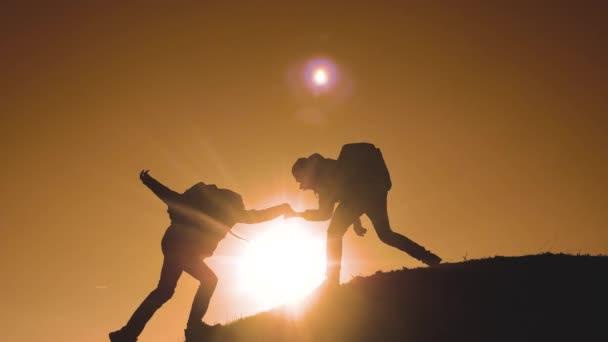 Týmová práce lidí turisté obchodní cesty cesty podává pomocnou ruku. dva muži s batohy turistické pomoci každé jiné silueta životní styl v horách s slunečního světla. zpomalené video. Týmová práce