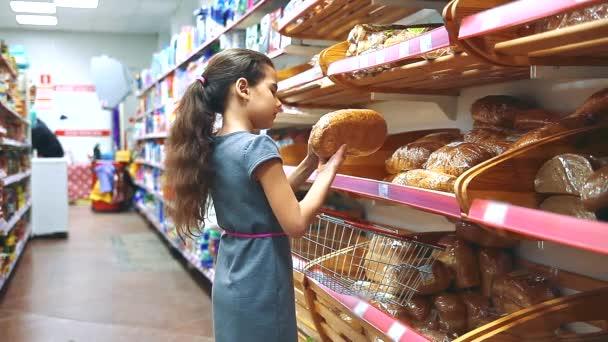 Holčička s digitálním tabletu v obchodě si koupí chleba pečivo pekařské produkty online. malá holčička v životní koncept hypermarket